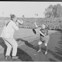 archival black-and-white photo depicting two men playfully shouting at one another through megaphones; from the National Archives of Norway, shot at a soccer game in 1955
