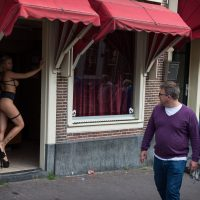 A man and woman pass a prostitute posing in a doorway in Amsterdam's red-light district