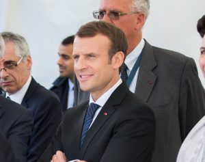 Color photo of President Emmanuel Macron of France visiting L'Ecole Polytechnique in Paris in October 2017. Macron is photographed from the chest up, wearing jacket and tie and flanked by unidentified dignitaries.