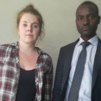 Image of Martha O'Donovan, wearing a flannel shirt and standing beside her lawyer, Odey Shava, who is wearing a dark suit and tie