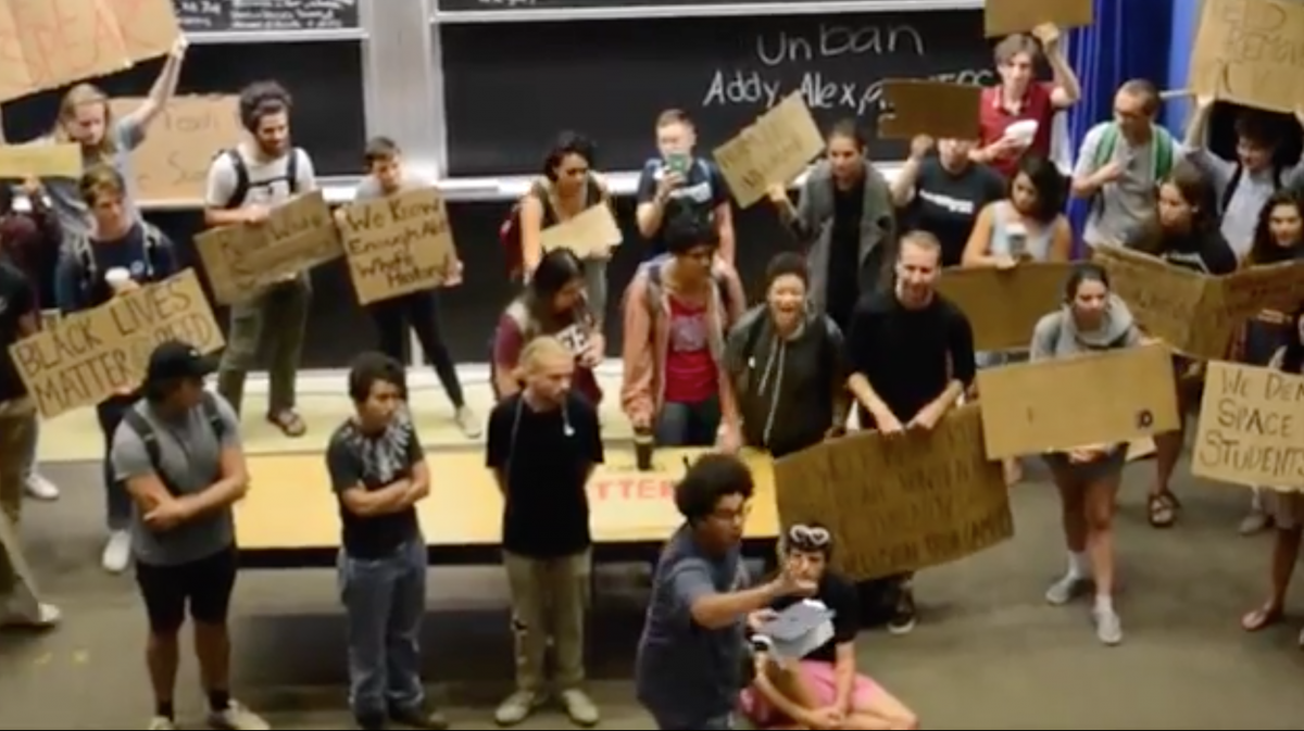 Screenshot of Reed College lecture hall with students standing up to demonstrators attempting to disrupt a Humanities 110 class that's required for all incoming freshmen