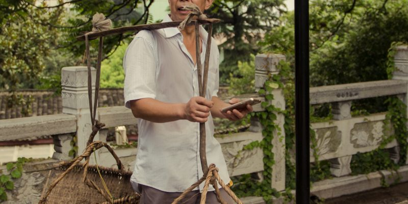 color photo of a Chinese man in the city of Wuhan, toting a yoke with two handmade carrying baskets in one hand and a smartphone in the other