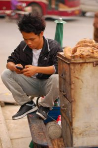 photo of a young Chinese vendor at the Nanning Bird and Flower Market in Nanning, China, squatting next to his sweet-potato cart, using his cell phone