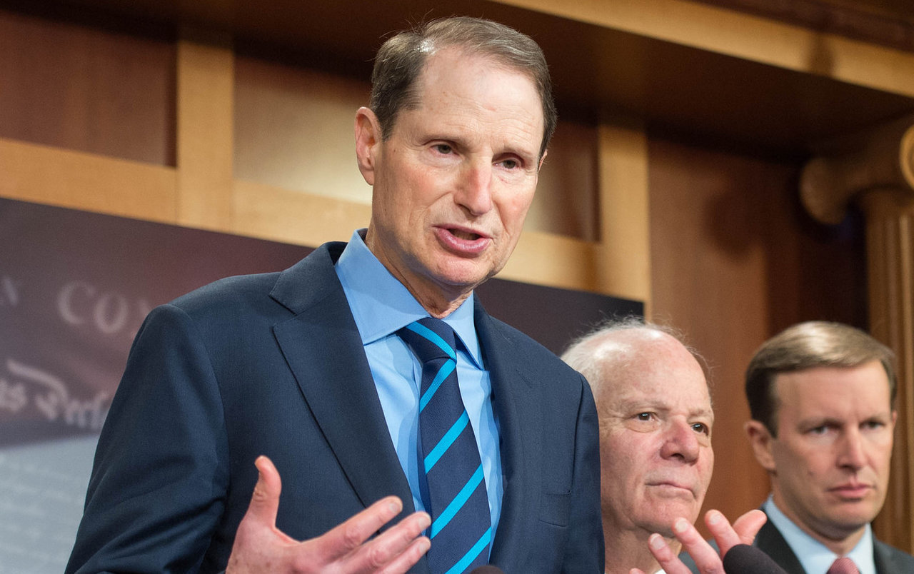 Ron Wyden in suit and tie, speaks and gesticulates at a podium in the U.S. Capitol building