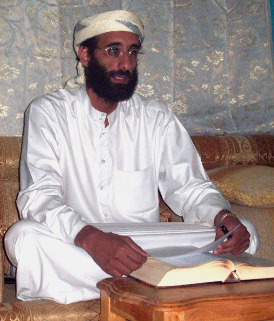 Color image of a bearded man in white robe and turban, seated cross-legged on a couch with an open book in front of him