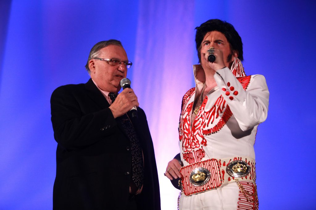color photo of Maricopa County Sheriff Joe Arpaio, dressed in suit and tie and appearing to sing alongside an Elvis impersonator at a convention in Phoenix in 2014