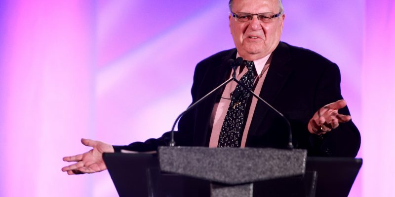 color photo of Maricopa County Sheriff Joe Arpaio, dressed in suit and tie, speaking at a convention in Phoenix in 2014
