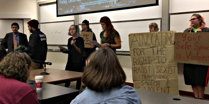 video screenshot of six students holding signs and protesting in a college lecture hall, while others -- including the visiting speaker -- look on.