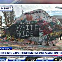 "A screenshot from a TV news report, showing a large boulder on the University of Tennessee's campus, painted over with an assortment of spray-painted graffiti, including the words ""White Pride"" in large white capital letters"