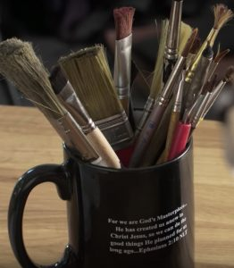 "close-up image of Jack Phillips's paintbrushes in a coffee mug bearing a verse from Ephesians 2:10 - ""For we are God's masterpiece. He has created us anew in Christ Jesus, so we can do the good things He planned for us long ago."""
