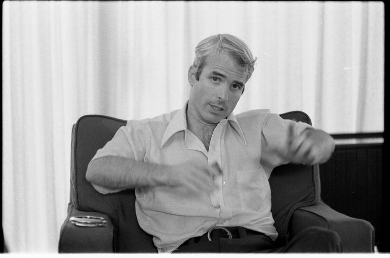 Black-and-white photo of John McCain, seated, in shirtsleeves, gesturing awkwardly during an interview in 1973. . Owing to injuries from physical torture, he would be forever unable to raise his arms above shoulder level.