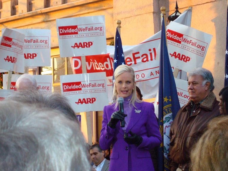 Color photo of Cindy McCain, wearing a bright purple coat and black gloves, against a backdrop of signs touting dividedwefall.org and the AARP, campaigning on behalf of her husband in the New Hampshire primary race, January 2008