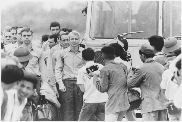 Black-and-white photo of John McCain and other newly released POWs in Vietnam