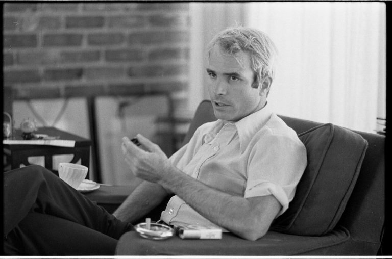 black-and-white photo of John McCain, seated, in shirtsleeves, during an interview in 1973