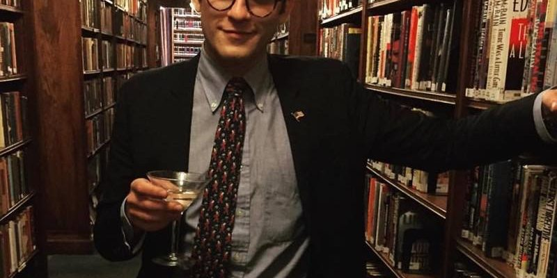 Color photo of Lucian Wintrich in jacket and tie in a library, holding a martini