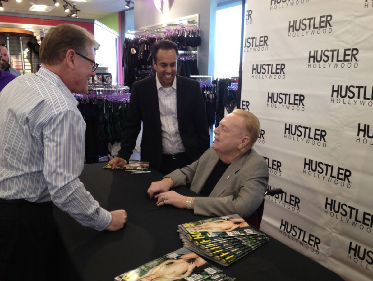 Larry Flynt, seated behind a table arrayed with copies of Hustler magazine, converses with two men at the opening of a Hustler Hollywood store in Phoenix, Arizona