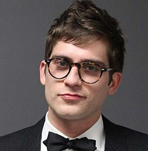Color mugshot of Lucian Wintrich sporting a bow tie and round, horn-rimmed glasses