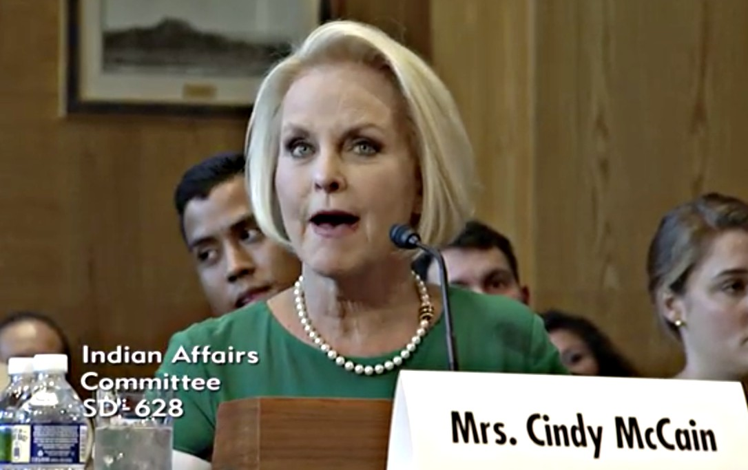 "A middle-aged woman, wearing pearls and a dress, in mid sentence, the name ""Mrs. Cindy McCain"" on a name sign in front of her."