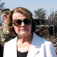 U.S. Senator Dianne Feinstein of California, outdoors, in dark sunglasses, inspecting damage from California wildfires; debris can be seen in the background, behind a soldier in camo fatigues whose face is mostly obscured by Feinstein