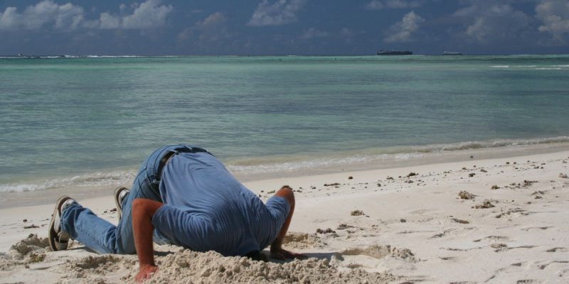 Image of a man in jeans and a short sleeved shirt on his knees on a beech with his head in the sand.