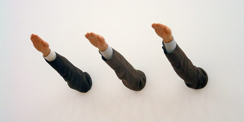 color photo of an art installation consisting of three disembodied arms giving the Hitler salute, protruding from a blank wall.