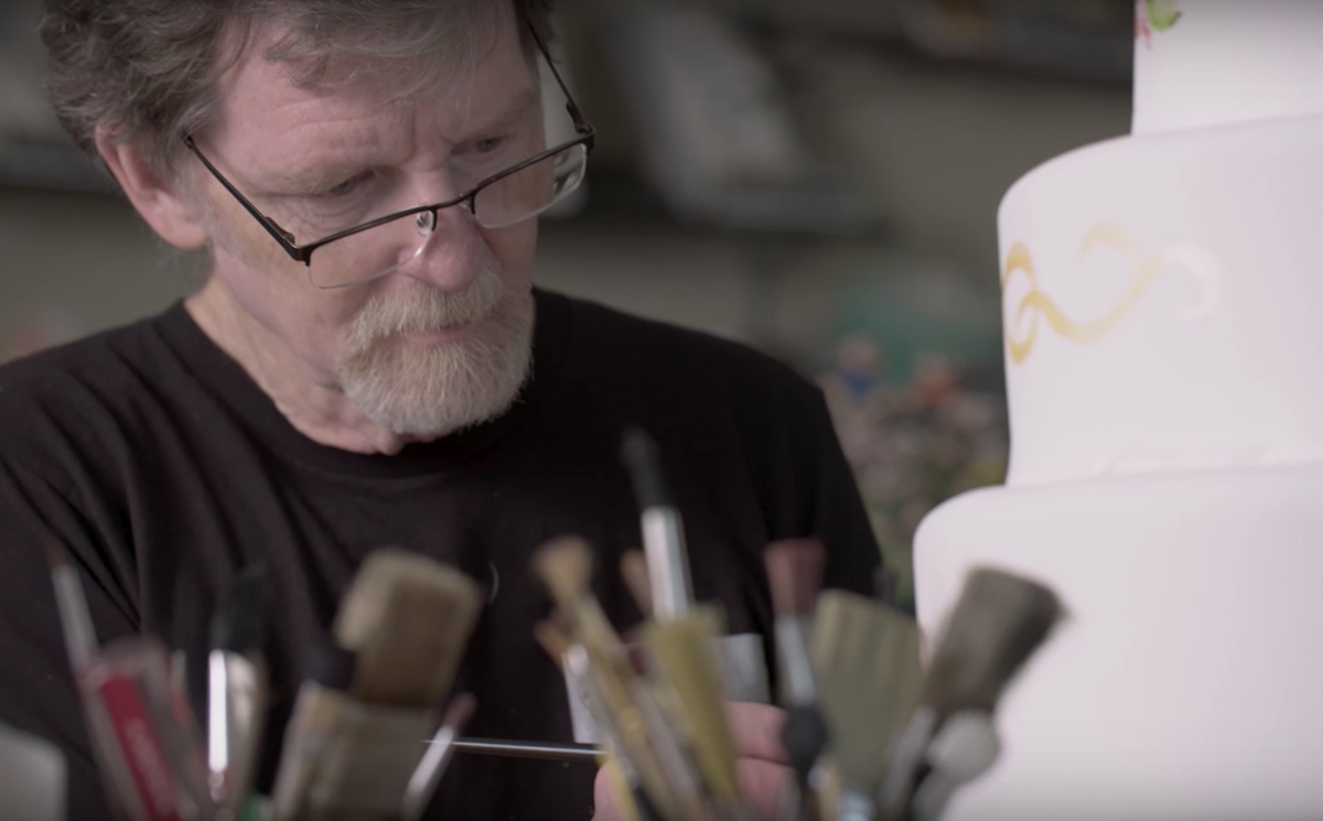 YouTube screenshot of Masterpiece Cakeshop owner Jack Phillips, goateed and wearing reading glasses perched on the bridge of his nose, decorating a wedding cake with a paintbrush
