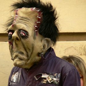 A person wearing a grotesque, rubbery Frankenstein's monster Halloween mask