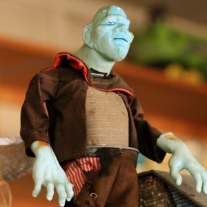 Close-up color photo of a Frankenstein toy with misshapen head, enormous hands, and ragged clothes
