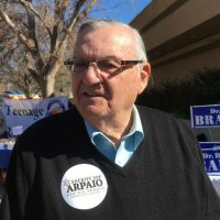 "Color photo of former Maricopa County sheriff Joe Arpaio sporting an ""Arpaio for U.S. Senate"" sticker on his V-neck sweater"