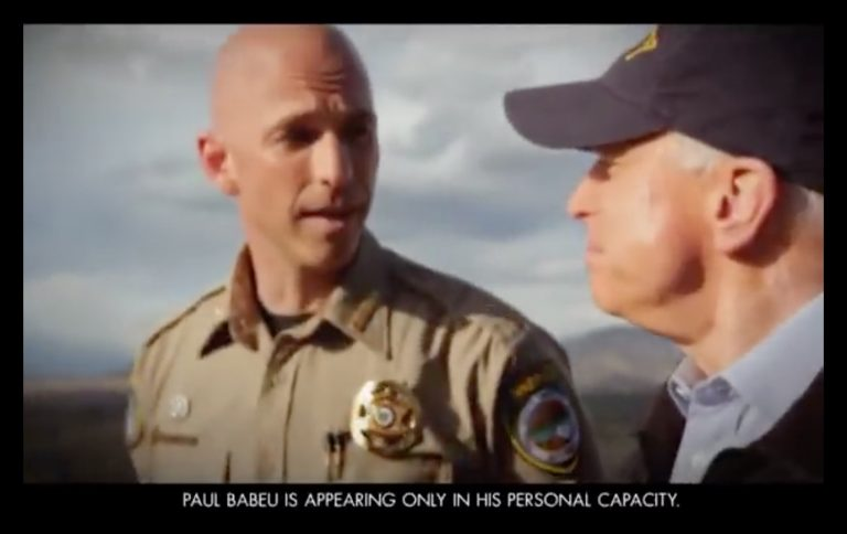 "YouTube screenshot of McCain in a TV spot alongside Pinal County Sheriff Paul Babeu, a well-known anti-immigration nativist. Babeu appeared in the ad in uniform, with a disclaimer that read ""Paul Babeu is appearing only in his personal capacity"""