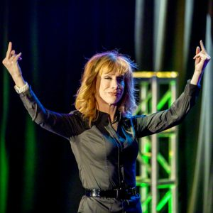color photo of comedian Kathy Griffin onstage, delivering a middle-finger salute to an unseen audience
