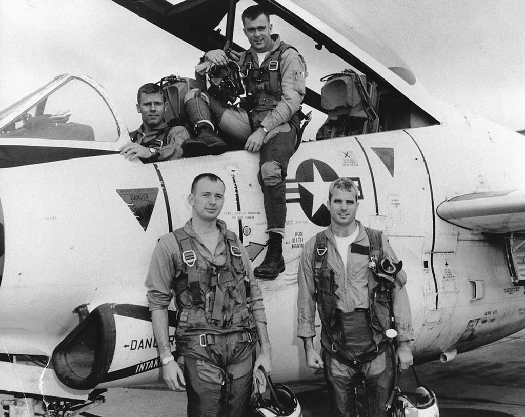Black-and-white photograph of John McCain and three fellow members of his U.S. Navy air squadron, posing in front of and in the cockpit of a jet