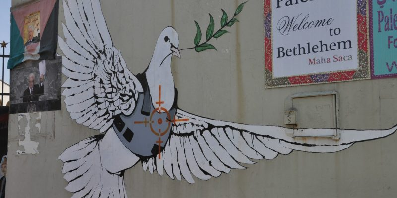 Color photo of a wall plastered with an image of a dove with olive branch in beak, wearing a flak jacket, with a gun's crosshairs on its breast.
