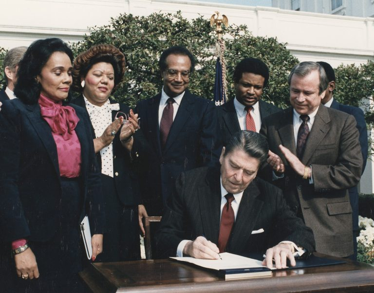 color photo of Ronald Reagan signing into law a national holiday to honor Martin Luther King, Jr., on November 2, 1983. Visible behind Reagan are (from left) George H.W. Bush, Coretta Scott King, Indiana Congresswoman Katie Hall, HUD Secretary Samuel Pierce, [unidentified], and Senate Majority Leader Howard Baker