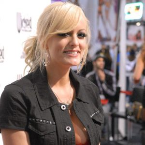 Color photo of porn actress Stormy Daniels, fully clad, during a 2010 appearance at the Adult Entertainment Expo in 2010