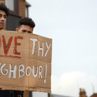"Color photo of counterprotesters at a Britain First demonstration in November 2014. Two men hold a hand-lettered cardboard sign that reads: ""Love Thy Neighbour"""