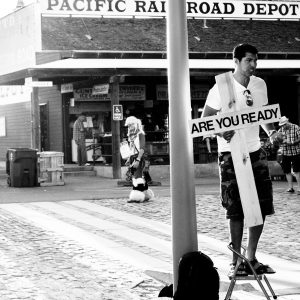 """black-and-white photo of a young man dressed in t-shirt and camo shorts, standing on a step-stool, holding a large cross that says, """"Are You Ready"""""""