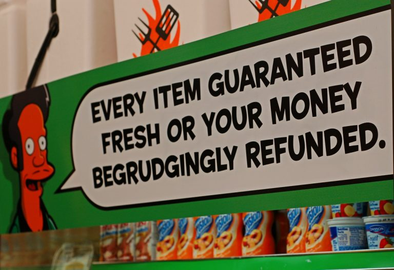 "photo of supermarket promotion for ""The Simpsons Movie,"" depicting the cartoon character Apu and a speech balloon that reads, ""Every item guaranteed fresh or your money begrudgingly refunded."""