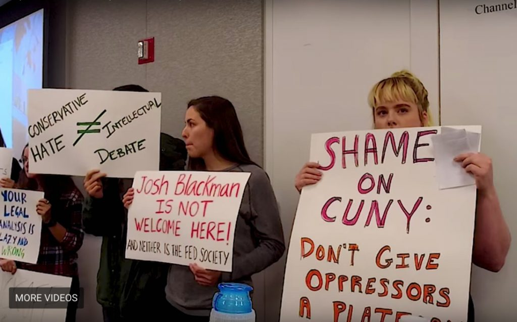 CUNY students hold signs in a classroom to protest a conservative law school professor's speech.
