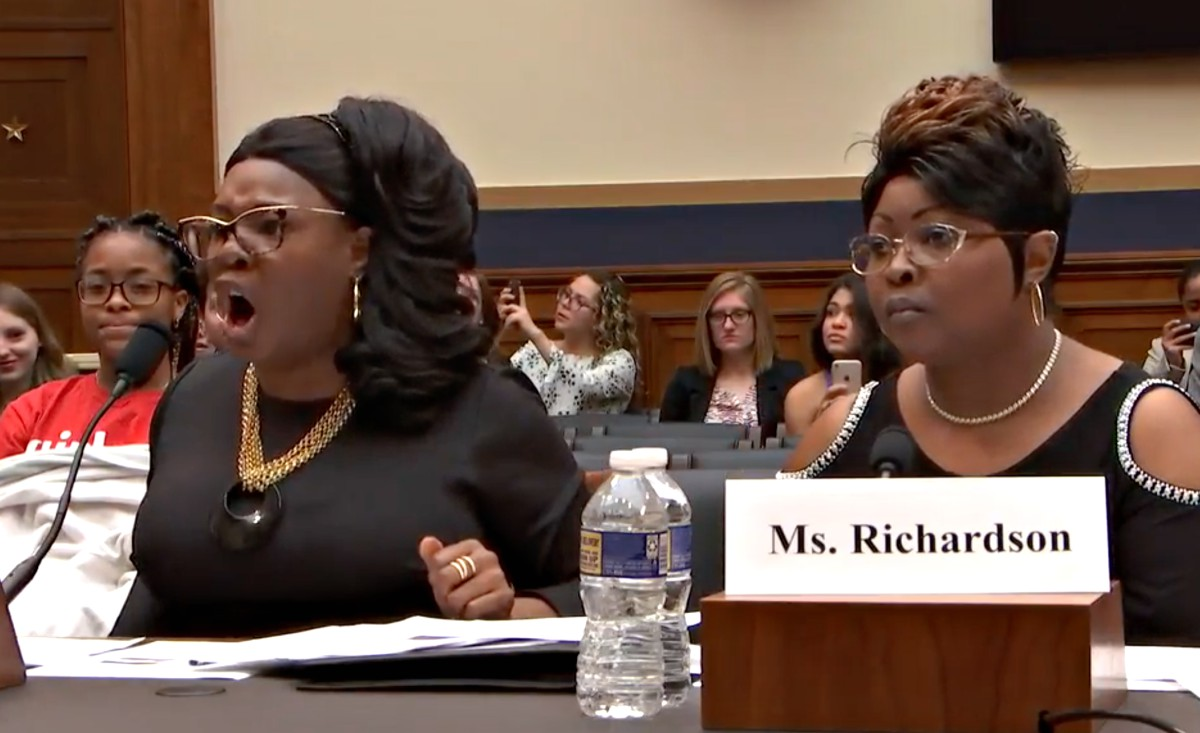 A screenshot of two African-American women (Diamond and Silk, whose real names are Lynnette Hardaway and Rochelle Richardson) -- seated at a table as they testify at a Congressional hearing