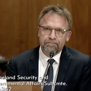 video screenshot of Backpage.com owner and CEO Carl Ferrer at a 2017 hearing of the U.S. Senate's Permanent Subcommittee on Investigations