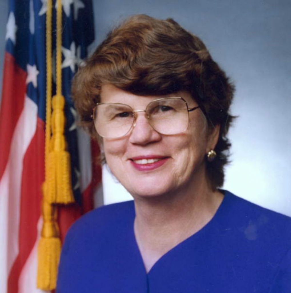 Official portrait of Janet Reno, middle aged woman wearing glasses with an American flag in the background.