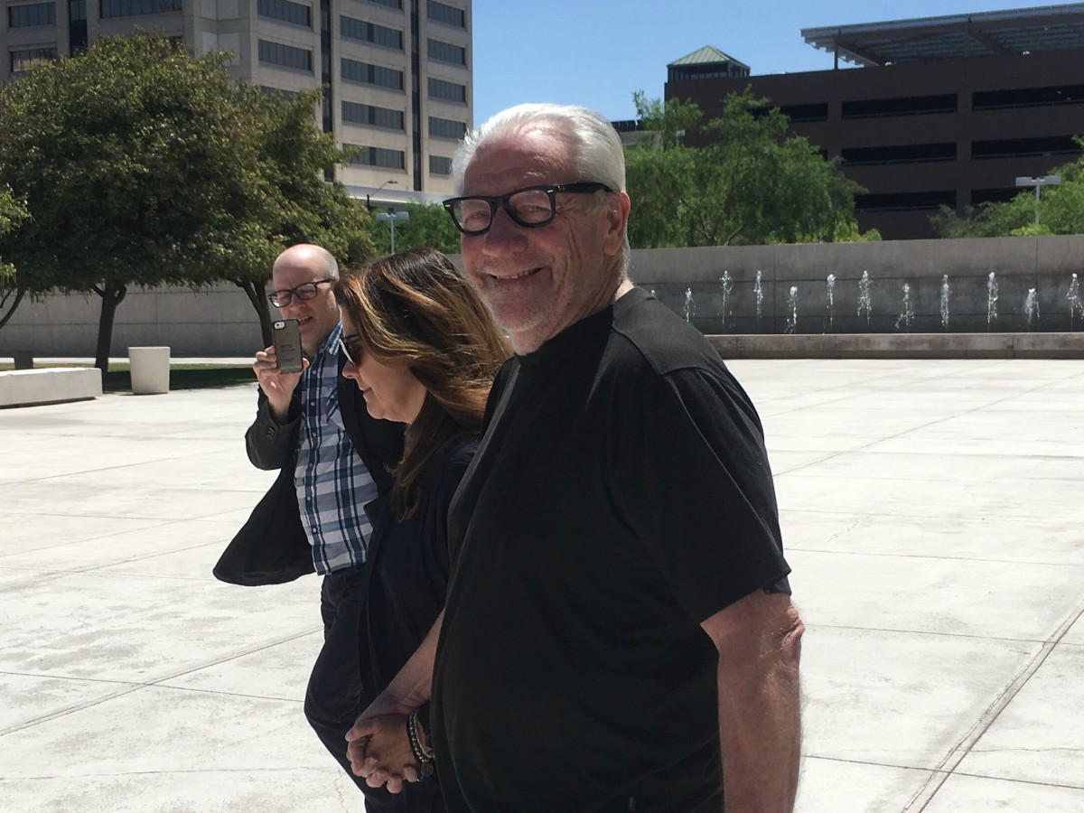 color photo of a grizzled, grinning Michael Lacey walking, hand in hand with his wife, as an unidentified reporter runs alongside, taking a picture with his phone.