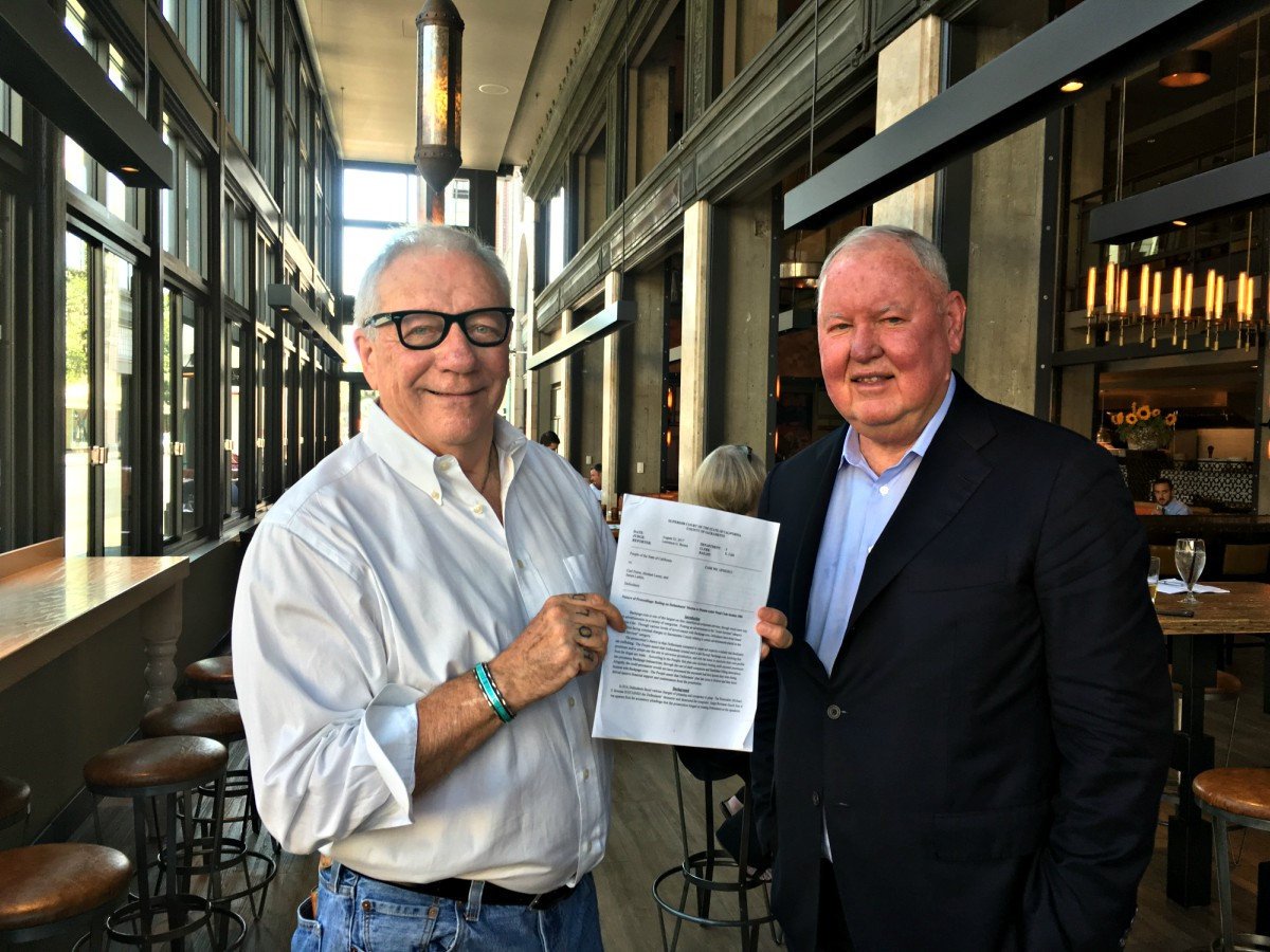 Color photo of Michael Lacey and Jim Larkin, standing in a restaurant, smiling and displaying a legal document.