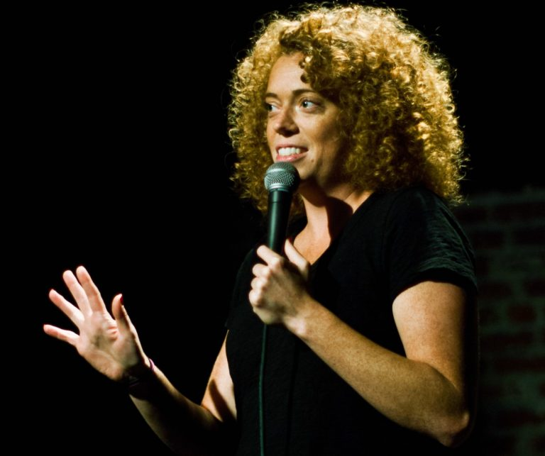 Color photo of comedian Michelle Wolf, holding a microphone