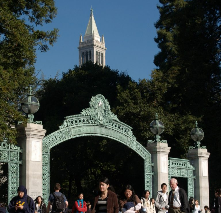 color photo of the Sather Gate at the University of California – Berkeley, with the top of the Sather Tower visible in the background