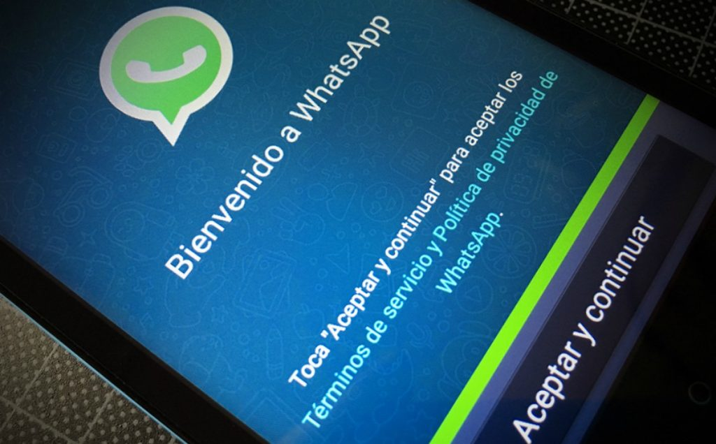 "Photo of an iPhone with an image of WhatsApp's icon with the words ""Welcome to WhatsApp"" in Spanish."