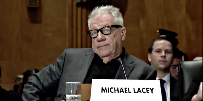 Michael Lacey, dressed in black and frowning, seated at a table in front of a microphone and a placard that bears his name