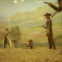 color photo of a diorama of the shootout at the O.K. Corral, featuring toy gunslingers on a dusty patch of dirt against a mountainous desert backdrop