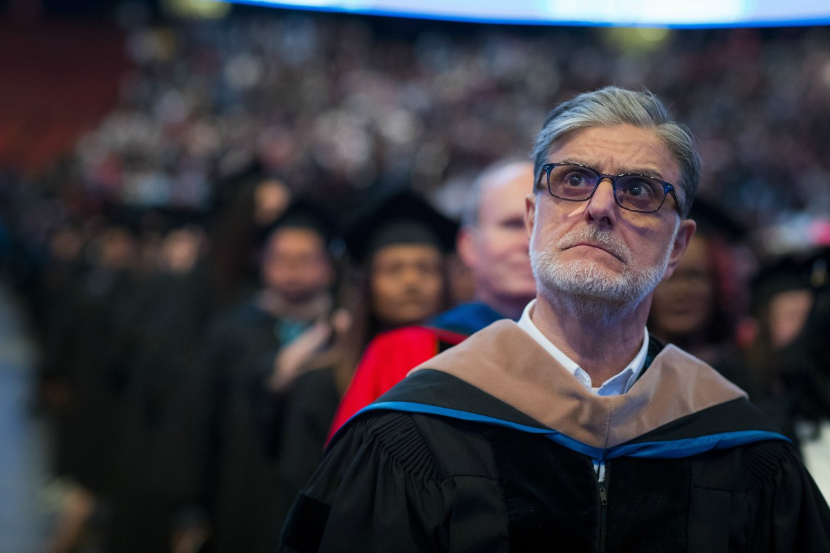 photo of a bespectacled middle-aged man at a graduation ceremony, wearing a professor's gown